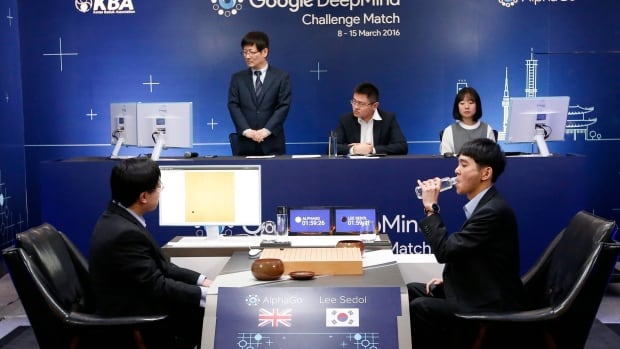 South Korean professional Go player Lee Sedol, right, drinks water after putting the first stone against Google's artificial intelligence program, AlphaGo, as Google DeepMind's lead programmer Aja Huang, left, sits during the match in Seoul on Wednesday.