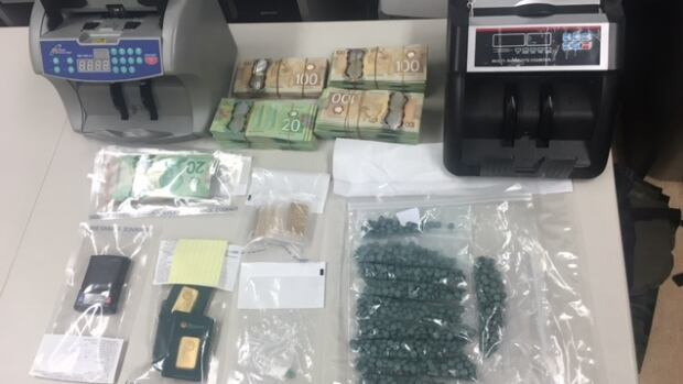 Fake OxyContin, cash, and powdered fentanyl were all recovered from a raid on a West Kelowna custom car shop on Auburn Road.