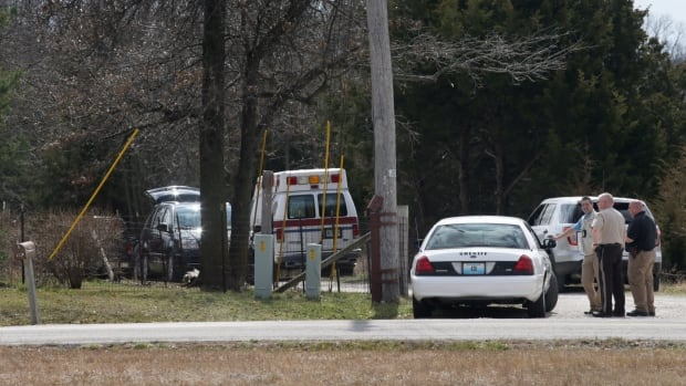 Police gather near the house where a man was found murdered on Tuesday near New Florence, Mo. Dozens of officers searched farmland in central Missouri on Tuesday for a man suspected of killing a man at a nearby house just hours after fatally shooting several people at his neighbour's home in Kansas.