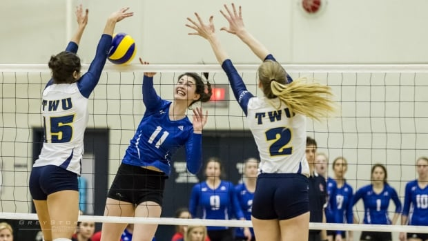 Katie Wuttunee (middle) from UBC Okanagan goes up against two players from Trinity Western University.