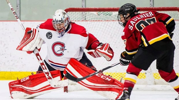 Les Montreal Canadiennes goaltender Charline Labonte stops Jillian Saulnier of the Calgary Inferno in Canadian Women's Hockey League action.