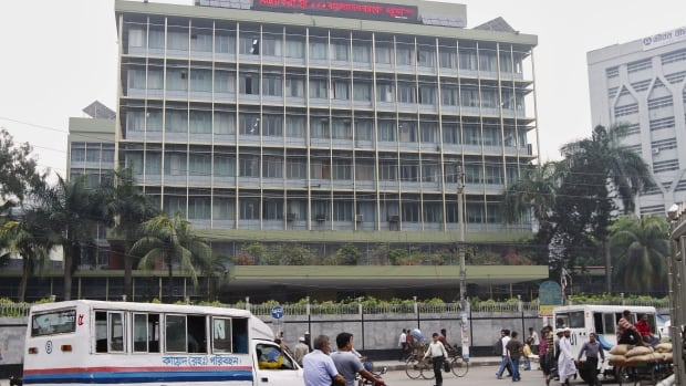 Commuters pass by the front of the Bangladesh central bank building in Dhaka on March 8, 2016.