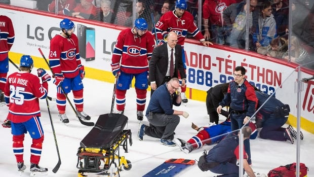 Montreal Canadiens players stand by while medical personnel prepare to remove the injured P.K. Subban who collided with teammate Alexei Emelin and was transported off the ice on a stretcher before being transferred to hospital.