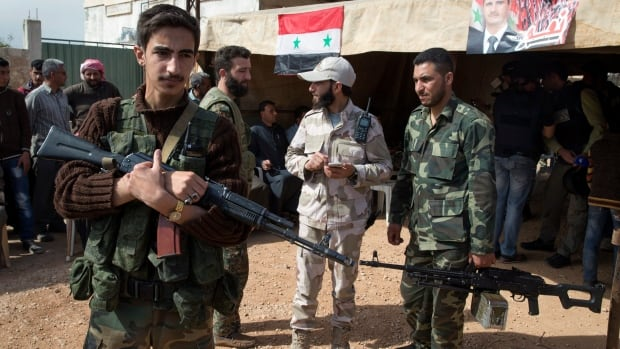 Syrian solders guard near a tent where local leaders and elders signed a declaration pledging to abide by a truce in Maarzaf, in this photo taken March 2, 2016. The government and the country's main opposition groups will have indirect peace talks in Geneva starting Monday.