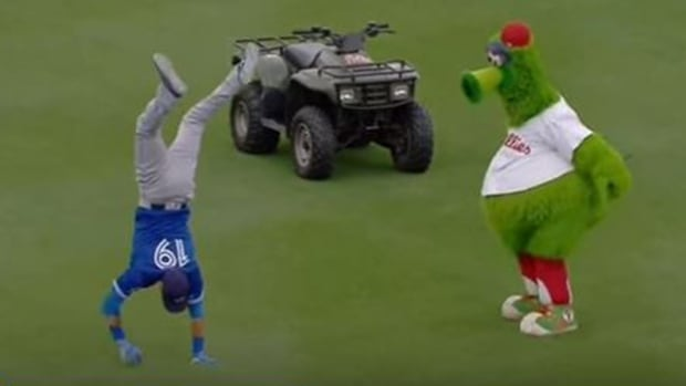 Jose Bautista, left, shows the Philadelphia Phillies' mascot how to execute a proper handstand.