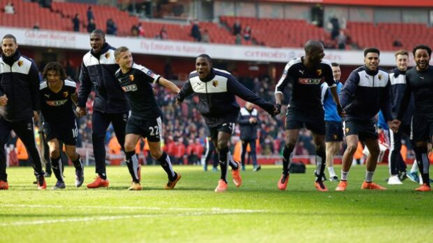 Watford players including their first goal scorer Odion Ighalo, centre, celebrate towards their fans after winning the English FA Cup quarter-final soccer match against Arsenal at the Emirates stadium in London on Sunday.