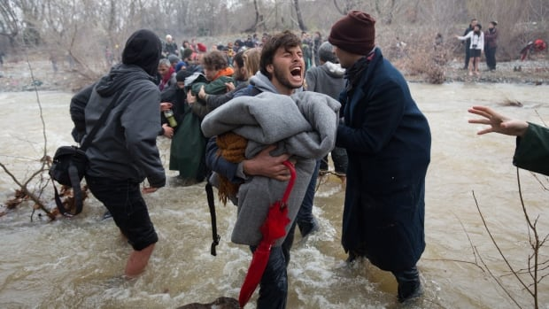 Migrants cross a river as they try to walk to the Macedonian border after leaving a refugee camp in Idomeni, Greece on Monday.
