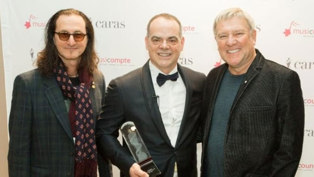 Fredericton High School teacher Don Bossé (centre) was surprised with the award presentation in Toronto last week by Rush members Geddy Lee and Alex Lifeson.