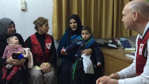 Conrad Sauve, president and CEO of the Canadian Red Cross, visits patients of a clinic supported by the Canadian Red Cross in Syria.