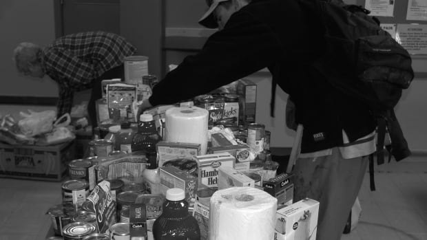 A man handles donated food at the Revelstoke food bank operated by Community Connections. Community Connections is doing a feasibility study to see if reclaiming food that would be thrown out by businesses would help with food security.