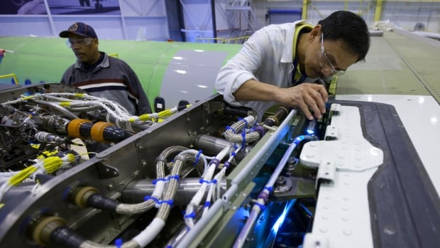A Bombardier worker looks over an engine at an aerospace plant near Toronto. Canadian factories cranked out a record number of sales in January, official numbers show.