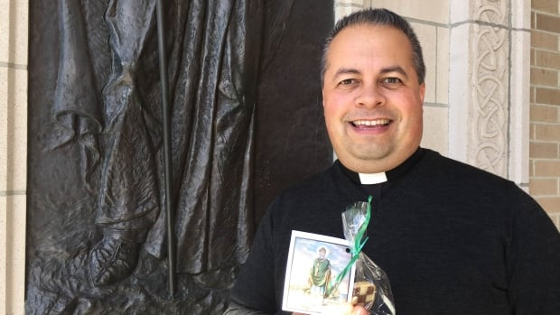 Father James Hughes of St. Patrick's Parish with one of the cookies and prayer cards his congregation will be handing out today.