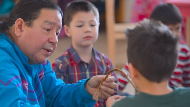 An Anishinabek elder teaches children at a First Nation-run school in Nipissing, Ont. Scenes like this could play out more often once a historic self-governing education curriculum is developed.