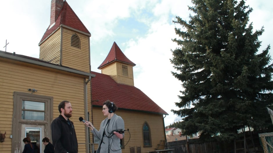 Chris Matthews, Executive Director of the Crowsnest Museum, speaks with the 180's Kathryn Marlow outside the old Holy Ghost Catholic Church. Matthews is part of a group leading a tour of empty buildings on April 16, 2016.