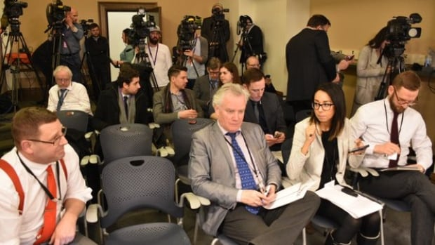 Members of the Alberta legislature press gallery await the start of a news conference.