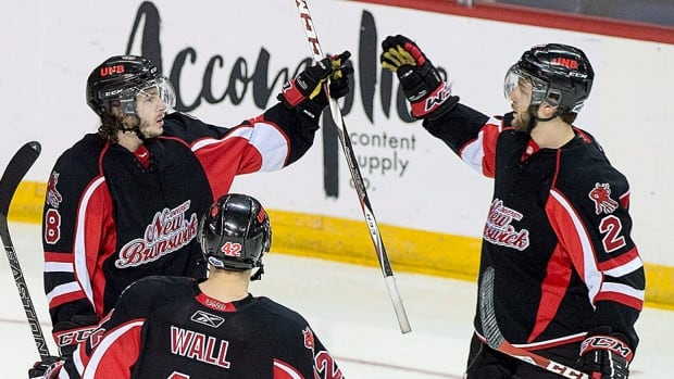 UNB Varsity Reds' Philippe Halley, middle, and his teammates celebrate his hat trick against the Western Mustangs in quarter-final CIS championship hockey action in Halifax on Friday. UNB won 5-1, with Matt Petgrave, while shorthanded, and Cameron Brace rounding out the UNB scoring.  Etienne Marcioux stopped 14 shots for the win.