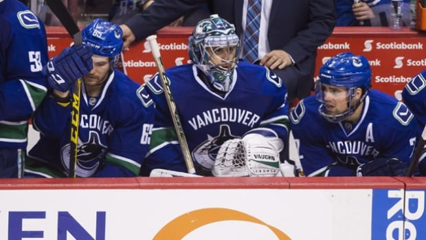 Vancouver Canucks' goalie Ryan Miller (30) sits on the bench with teammates Alexandre Grenier (65) and Dan Hamhuis (2) during third in Vancouver on Saturday.