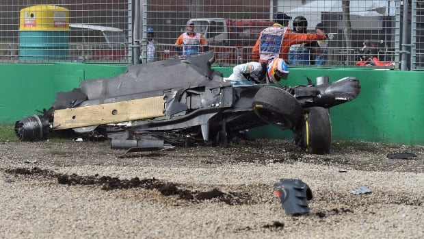 McLaren driver Fernando Alonso of Spain climbs out of his wrecked car after he collided with Haas driver Esteban Gutierrez of Mexico during the Australian Formula One Grand Prix at Albert Park in Melbourne, Australia, on Sunday, March 20, 2016.