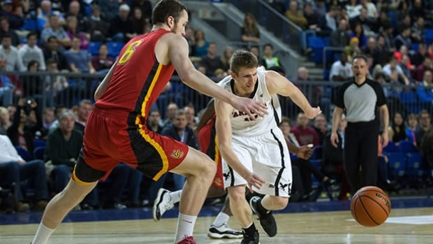 Carleton Ravens' Connor Wood, right, and Calgary Dinos' Dallas Karch chase after a loose ball during the CIS men's national university basketball championship final game in Vancouver, B.C., on Sunday.