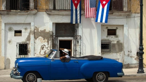 An old car passes by a house decorated with the flags of the United States and Cuba.  EPA/ORLANDO BARRIA