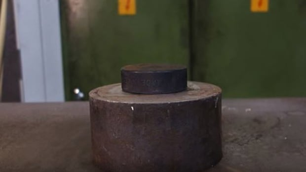 A hockey puck prepares to meet the crushing power of a hydraulic press.