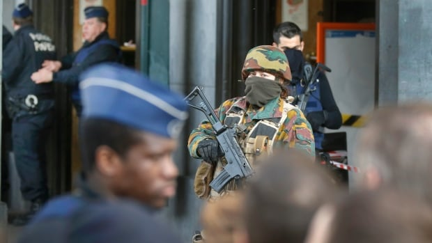 Police control the access to the central train station following three bombings in Brussels.