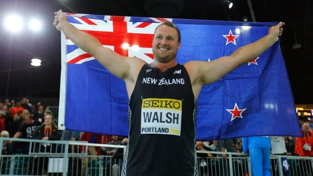 Tomas Walsh of New Zealand holds his country's flag on March 18 as he celebrates after winning the gold medal in the shot put during the IAAF World Indoor Athletics Championships in Portland, Ore.