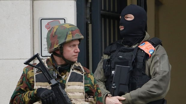 A police officer and a soldier stand guard outside the Council Chamber of Brussels on March 24, 2016.