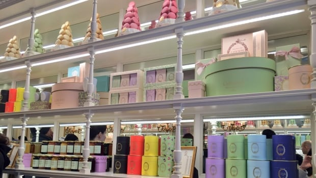 Macaron towers and a variety of teas line the shelves of Ladurée Vancouver.
