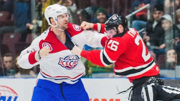 In this March 4, 2016 photo provided by the St. John's IceCaps, IceCaps player John Scott and Albany Devils' Ben Thomson fight during an AHL game in St. John's.
