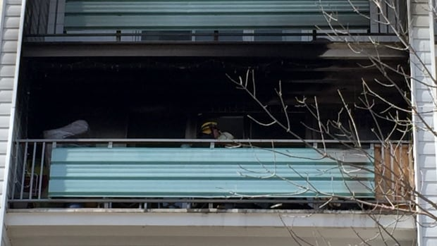 Fire crews inspect the balcony of an apartment on Henderson Highway Saturday afternoon after a fire.
