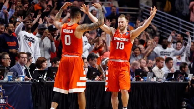 Syracuse's Michael Gbinije, left, and Trevor Cooney celebrate after defeating Virginia in the East regional final of the NCAA Tournament on Sunday in Chicago.