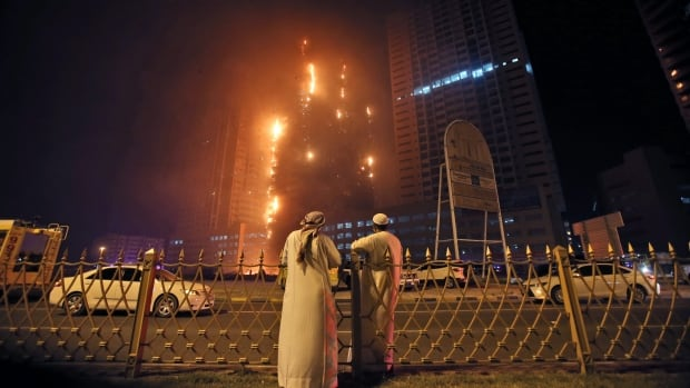 Two Emirati officials watch as fire spreads up the side of the building in Ajman, United Arab Emirates, early Tuesday.