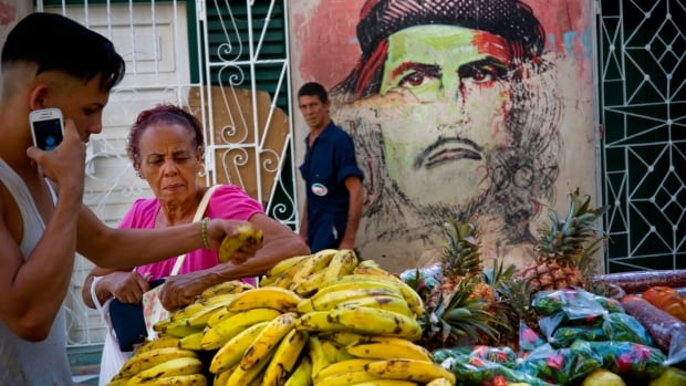 A Cuban fruit vendor attends to a client backdropped by a mural of Che Guevara in Old Havana. A rising entrepreneur class in the Caribbean island is emerging as Cuba opens up more possibilities for private enterprise.