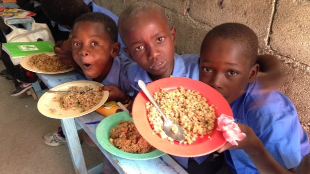 Three young boys show off their lunch of rice and lentils at Pastor Foglas's school feeding program.