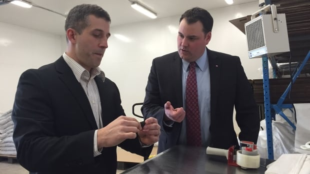 Jules LeBlanc (left), president of Ocean Pride Fisheries Ltd, shows dried sea cucumber to West Nova MP Colin Fraser today at a company plant in Wedgeport. Ocean Pride has been loaned $500,000 by ACOA.