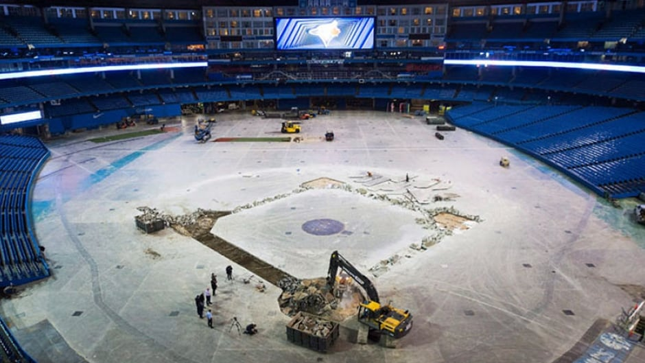 Construction workers hammer out concrete as they install the new dirt infield at the Rogers Centre in Toronto.