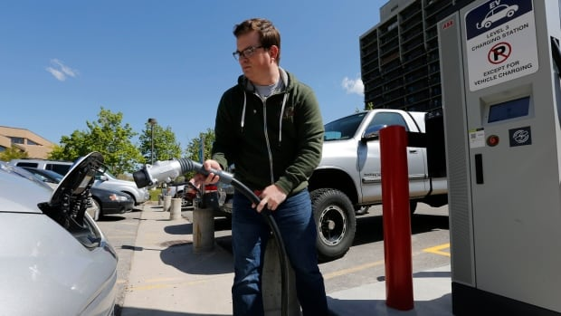 Justin Miller hooks up a charging cable to charge his 2013 Nissan Leaf electric car at ABB, Inc.'s DC fast charging station in Salt Lake City, Utah, April 30, 2014.