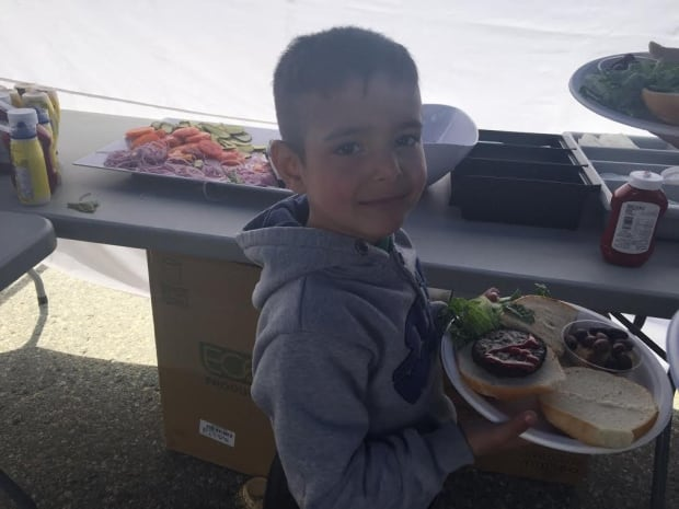 Syrian refugees on Mount Seymour eat BBQ