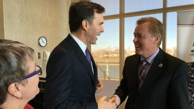 Finance Minister Bill Morneau greets Stratford Mayor David Dunphy as P.E.I. Transportation and Infrastructure minister Paula Biggar looks on.