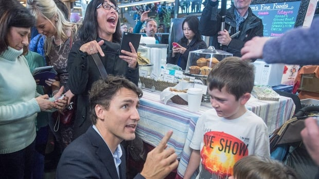 A bystander appears overwhelmed to be so close to Prime Minister Justin Trudeau as he talks with children at the Halifax Seaport farmers market on April 2.