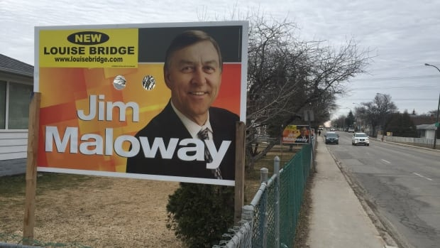Veteran Elmwood NDP MLA Jim Maloway has covered up his party's name on his campaign signs.