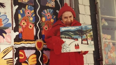 Maud Lewis posts with one of her paintings, standing in front of her art house.