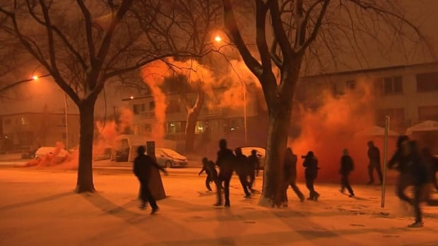 A group of protesters run past a smoke bomb set off during an anti-police brutality march in Montreal North on April 6.