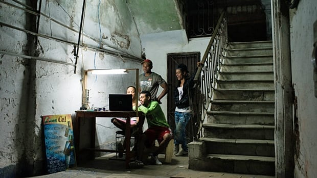 Men gather around a laptop to watch videos in a cellphone repair shop in Old Havana. Without widespread internet access, Cubans rely on 'el paquete,' the weekly package of digital media, delivered on USB thumb drives and external hard drives.