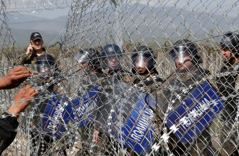 Migrants hit with tear gas at border fence between Greece