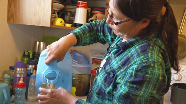 Maggie Sakanee pours water carried in a jug from the small, reverse-osmosis purification system in northwestern Ontario's Neskantaga First Nation, home to Canada's longest-standing boil-water advisory, in place for more than 20 years.