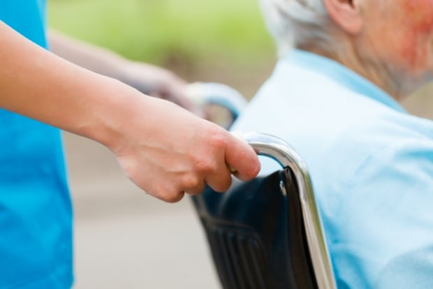 Care worker pushes elderly woman in seniors care home stock image