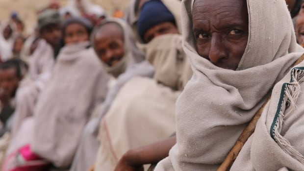 People wait for food aid at a distribution centre in northern Ethiopia. The aid is becoming ever more important as the drought rages on, leaving more than ten million Ethiopians vulnerable to food shortages.