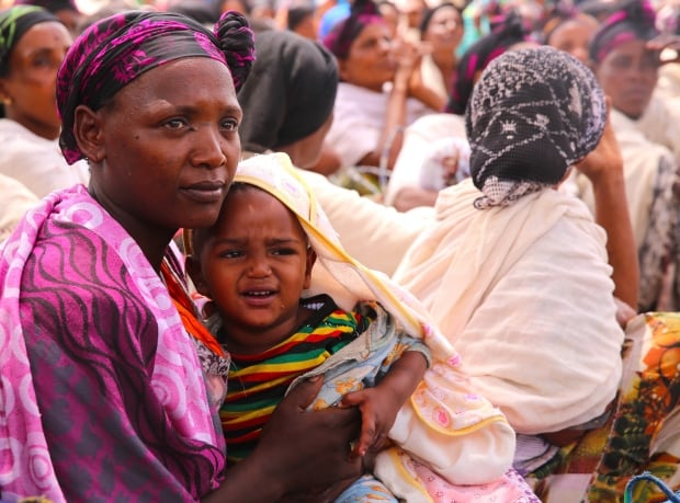 Mother and baby wait for food aid in Dugda, Ethiopia
